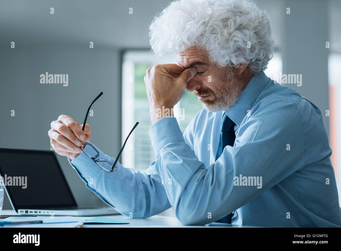 Stressed exhausted businessman sitting at office desk, failure and loss concept - Stock Image