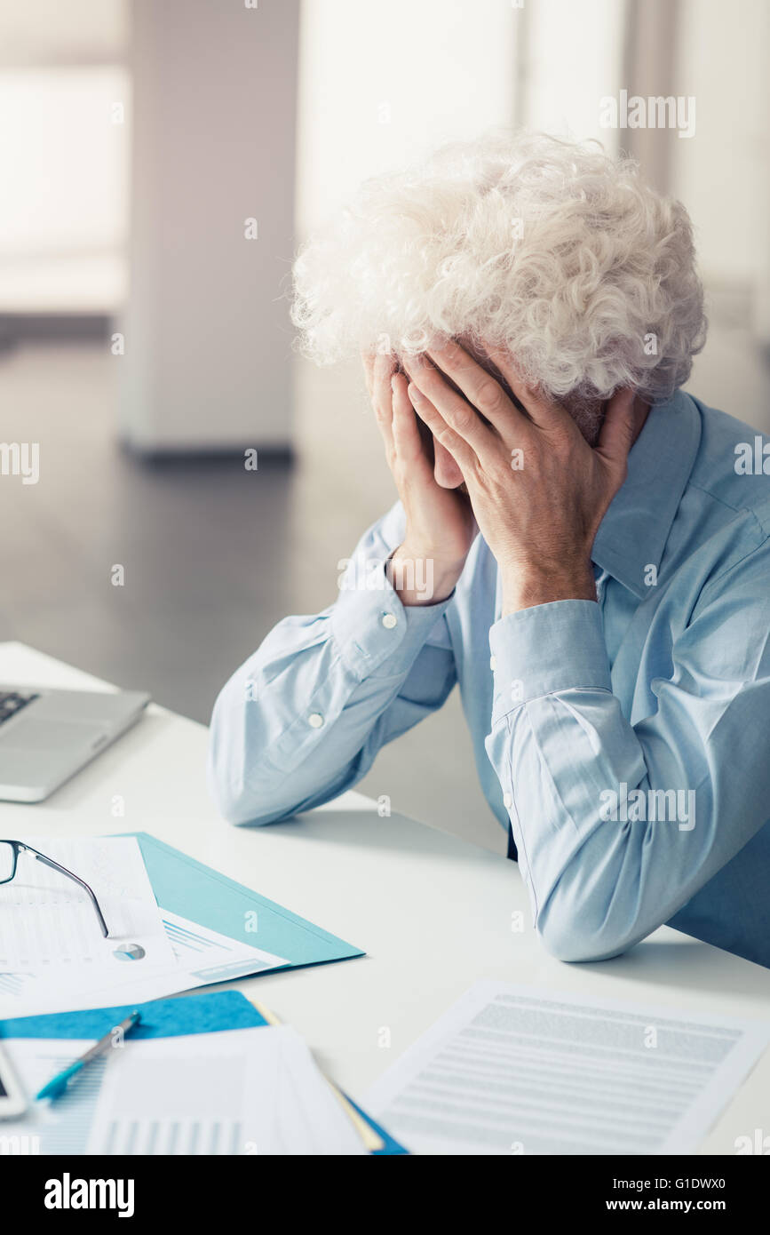 Exhausted businessman with head in hands sitting at office desk, failure and depression concept - Stock Image