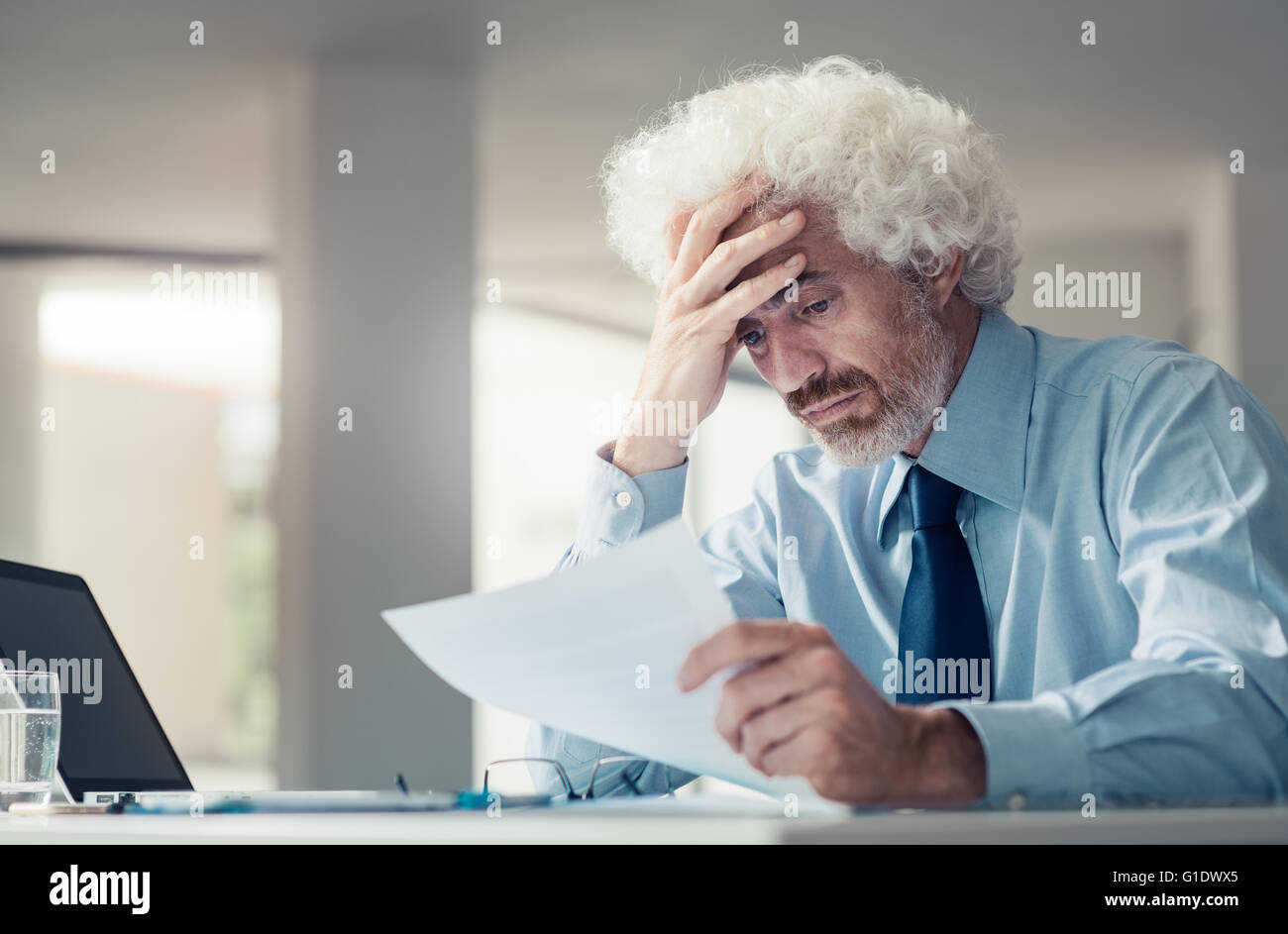 Confused shocked businessman receiving bad news, reading a letter and touching his forehead, failure and loss concept - Stock Image