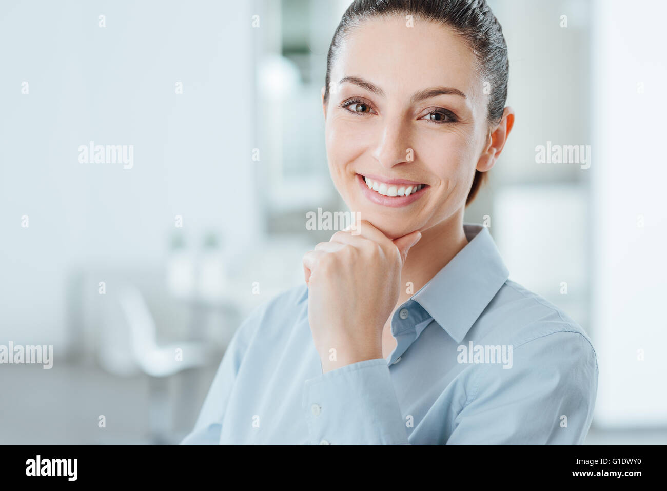 Pretty young woman posing with hand on chin and smiling at camera, room interior on background - Stock Image
