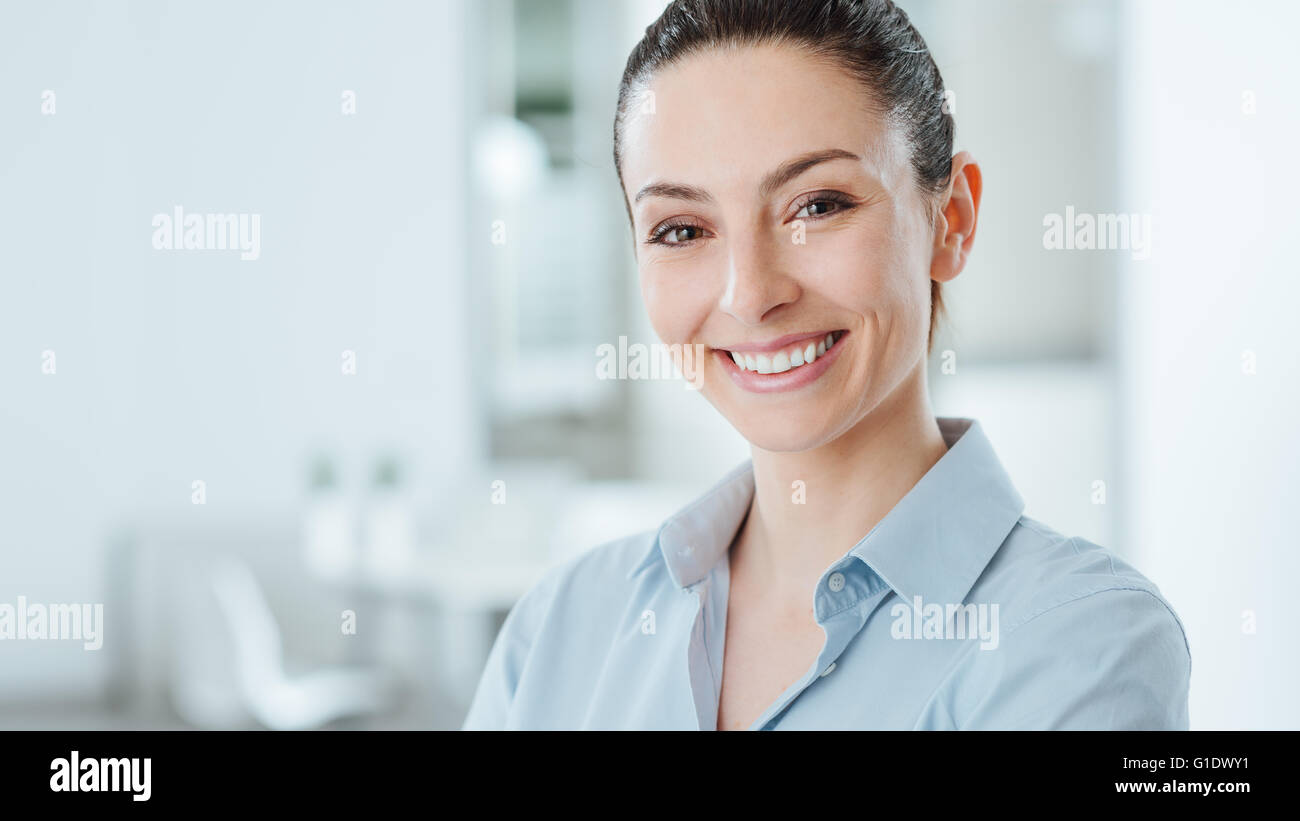 Beautiful confident business woman posing and smiling at camera, office interior on background - Stock Image