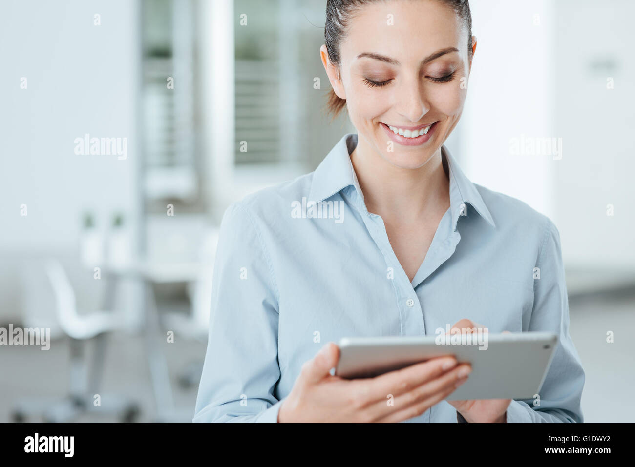 Young smiling business woman using a digital touch screen tablet and using apps, she is standing in the office - Stock Image