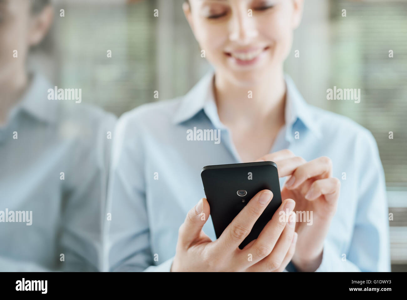 Beautiful smiling young woman using a smart phone, leaning on a window and reflecting on glass - Stock Image