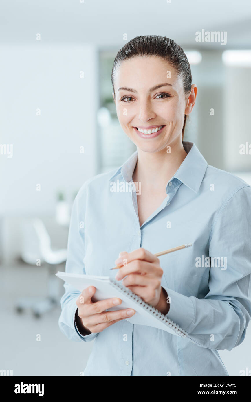 Young professional secretary writing down notes on a notebook and smiling at camera, she is standing in the office - Stock Image