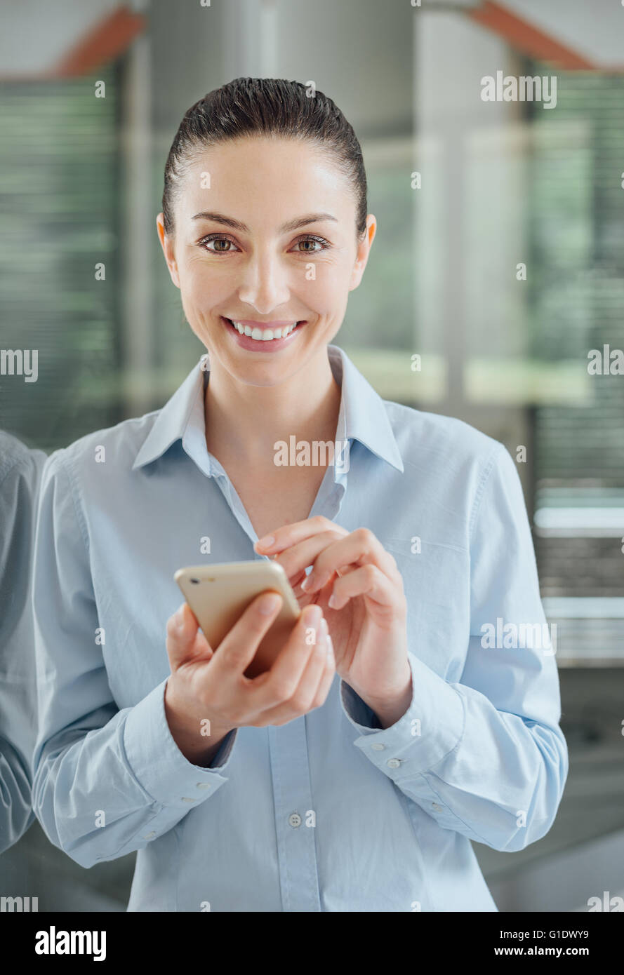 Beautiful young woman using a smart phone and leaning on a window, she is smiling at camera - Stock Image