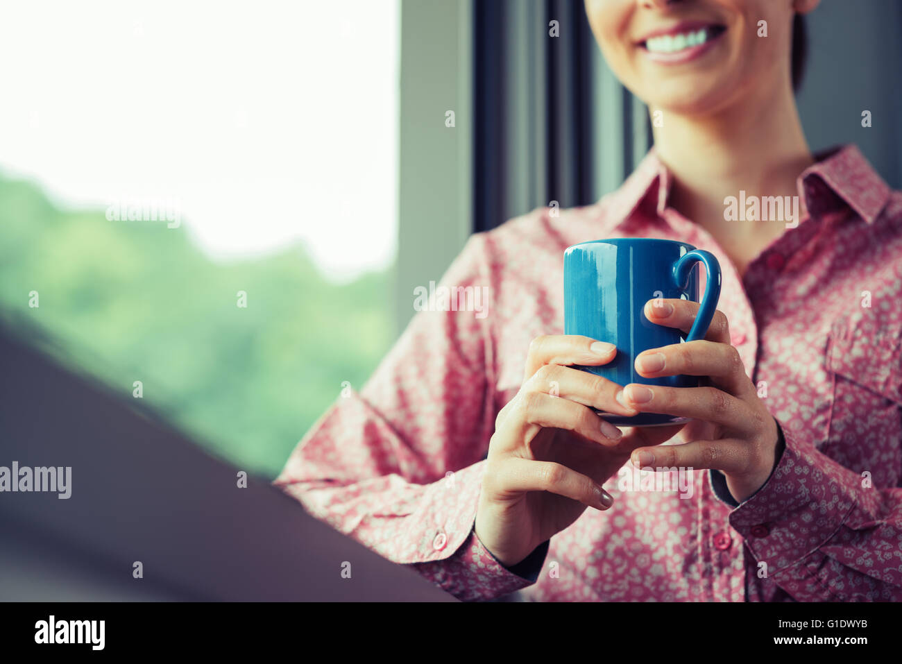 Woman having a relaxing coffee break at window, she is smiling and holding a mug - Stock Image