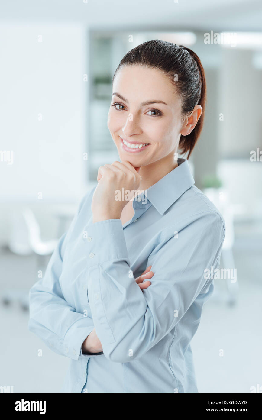 Confident woman posing with hand on chin and smiling at camera - Stock Image