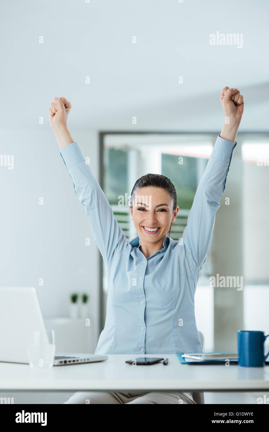 Successful cheerful businesswoman with fists raised sitting at office desk, achievement and satisfaction concept - Stock Image