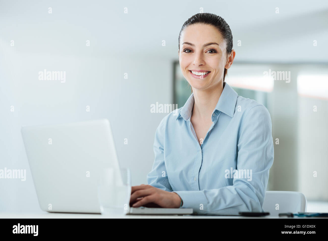 Smiling young businesswoman working at office desk and typing on a laptop, she is looking at camera - Stock Image