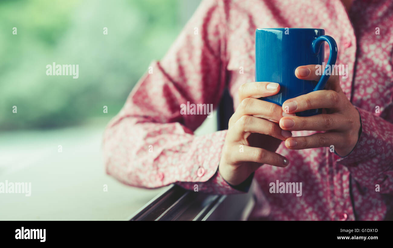 Woman at window holding a cup and having a relaxing coffee break, hands close up - Stock Image