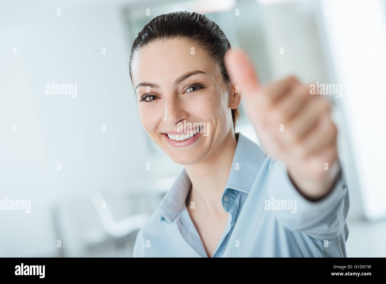 Beautiful businesswoman thumbs up smiling at camera, success and achievement concept - Stock Image