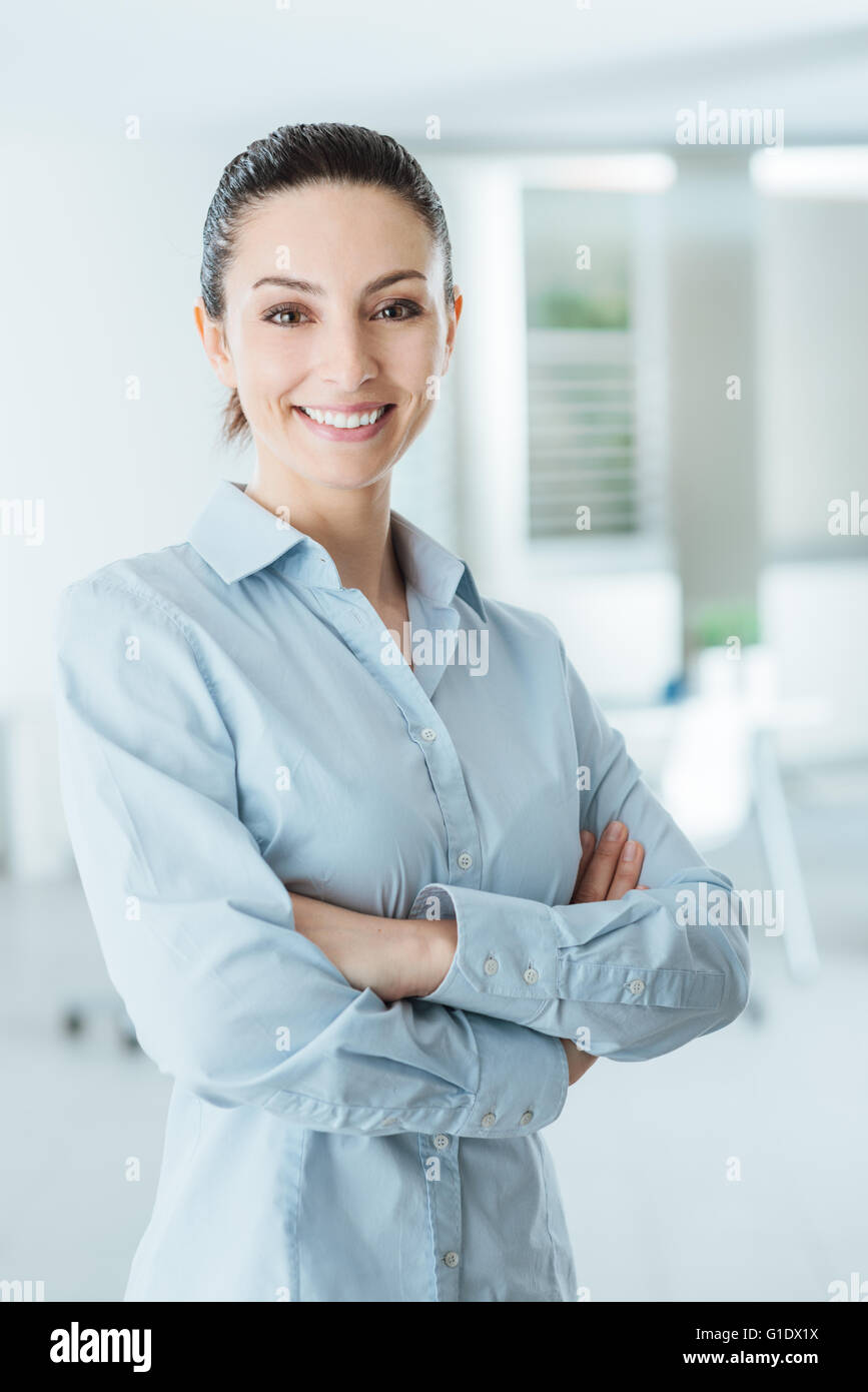 Beautiful confident business woman posing with crossed arms, smiling at camera and standing in her office - Stock Image