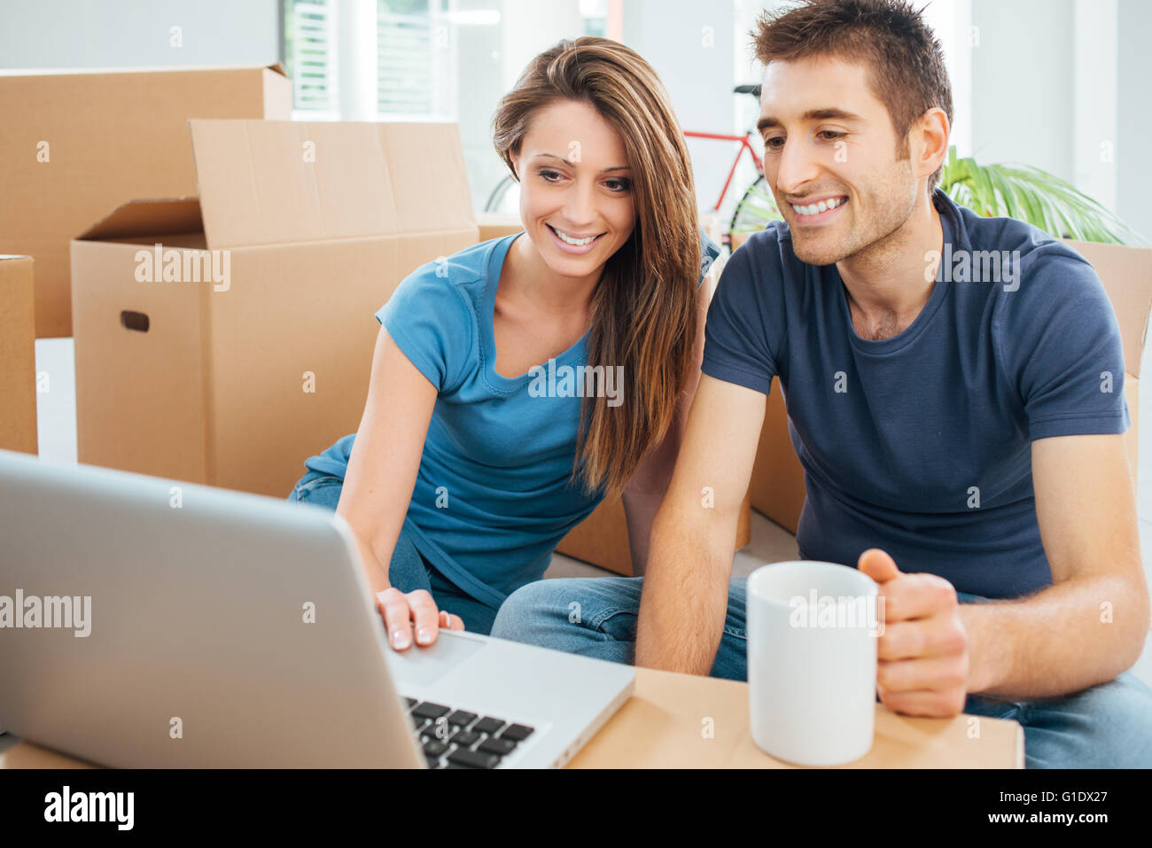 Happy couple sitting on their new house floor surrounded by carton boxes and using a wireless laptop during a coffee - Stock Image