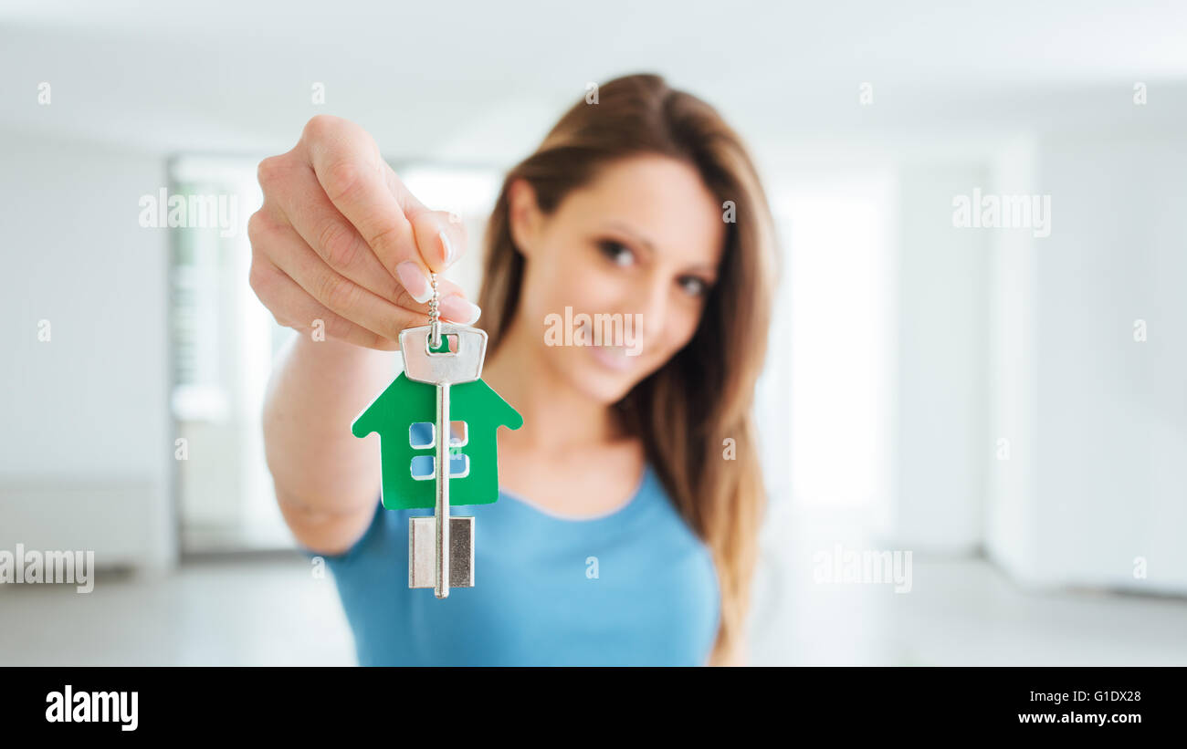 Beautiful smiling woman holding house keys of her new house, real estate and relocation concept - Stock Image