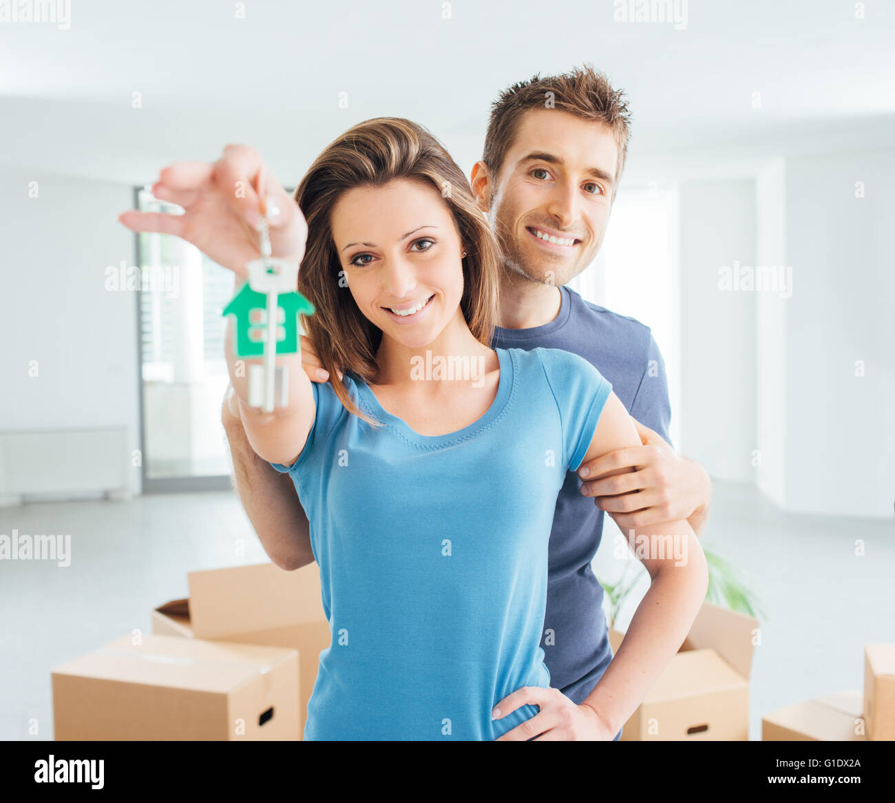 Young smiling couple holding their new house keys, real estate and relocation concept - Stock Image