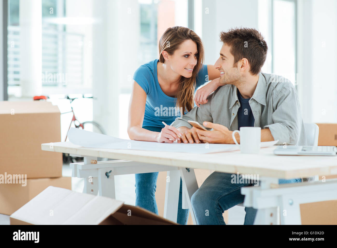 Romantic loving couple planning and designing their new house, they are staring at each other's eyes - Stock Image