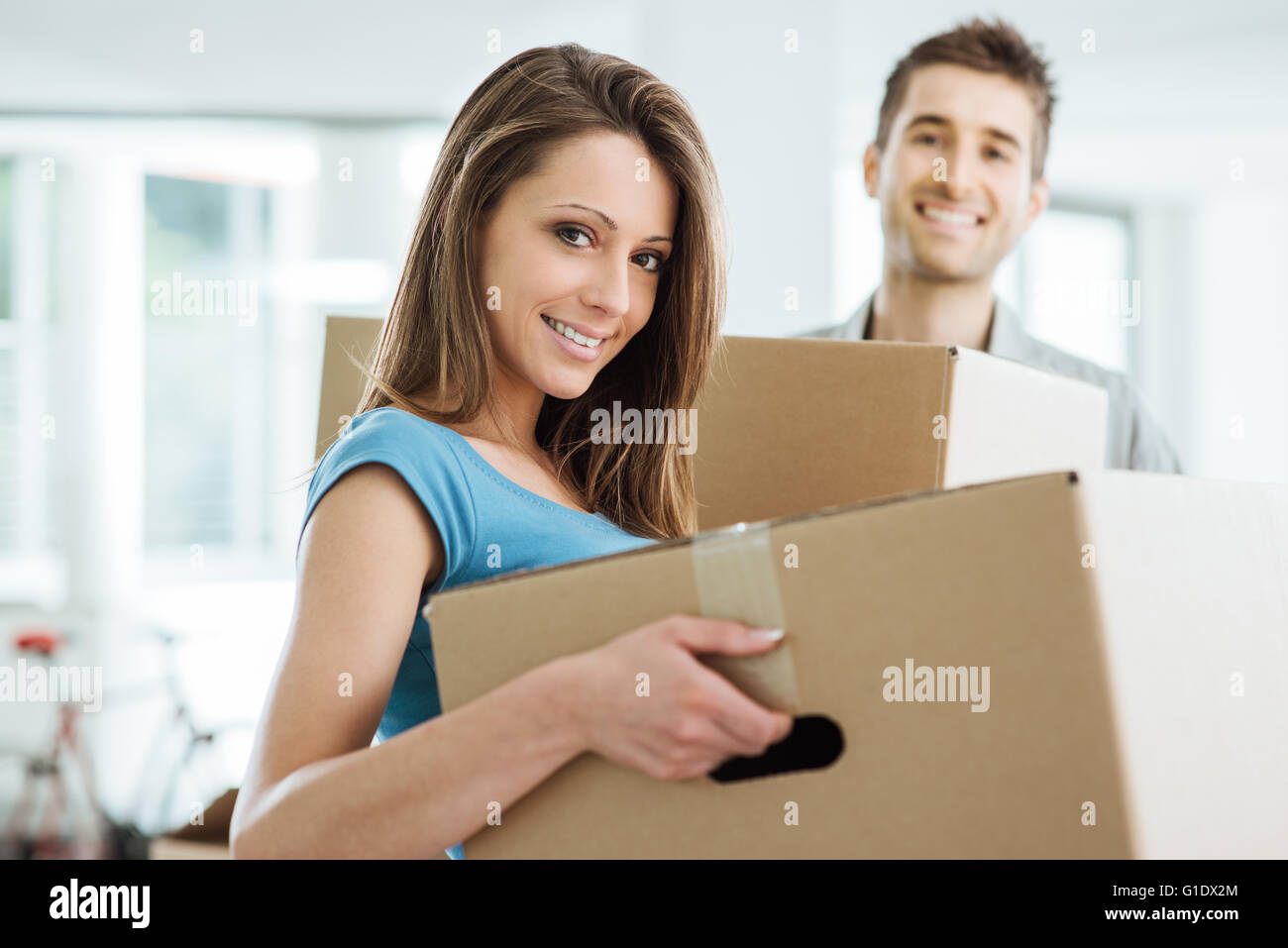 Happy smiling couple moving in a new house and carrying carton boxes, relocation and renovation concept - Stock Image