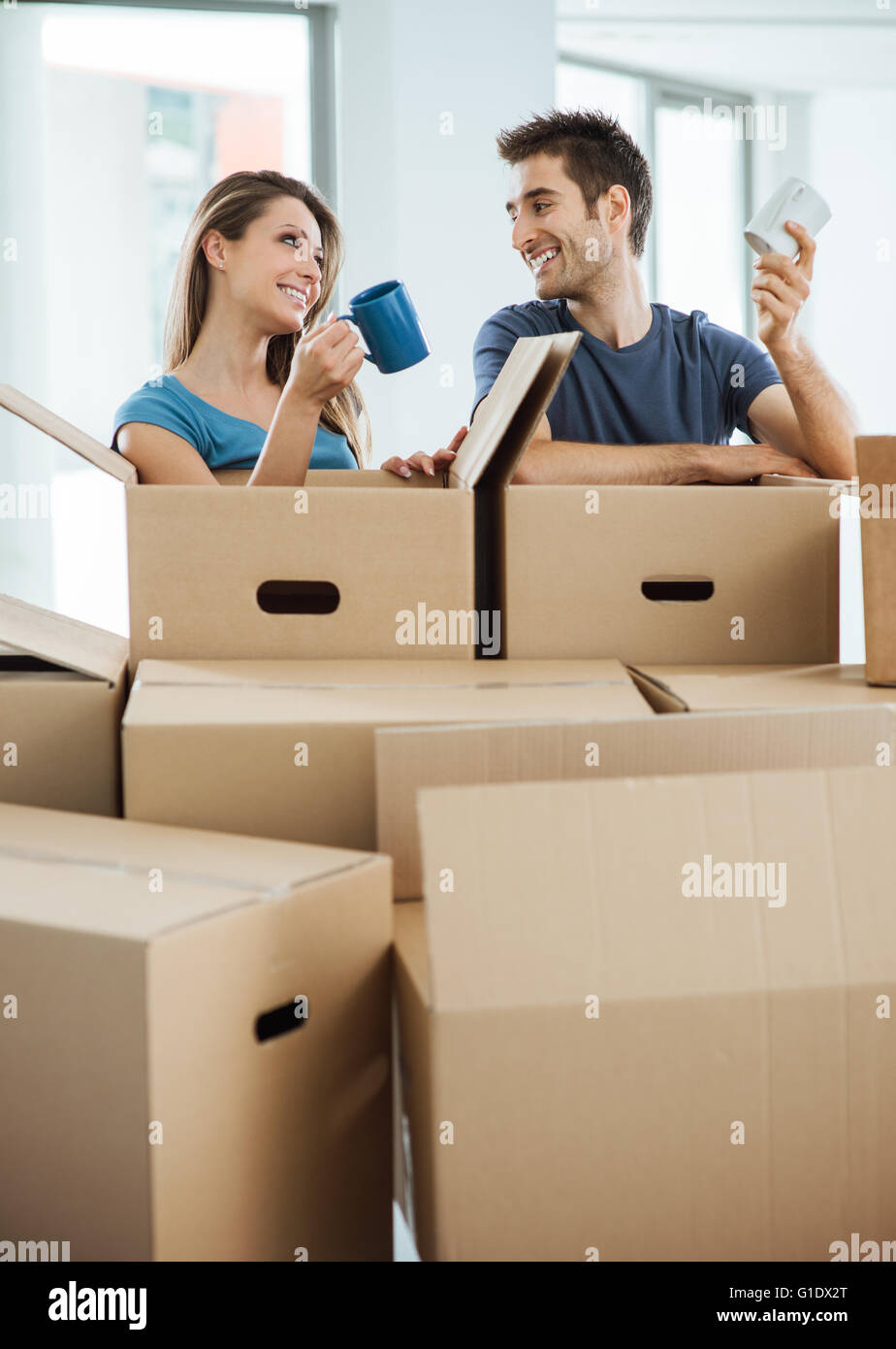 Happy couple having a coffee break during a relocation in their new house, they are holding a mug and smiling at Stock Photo