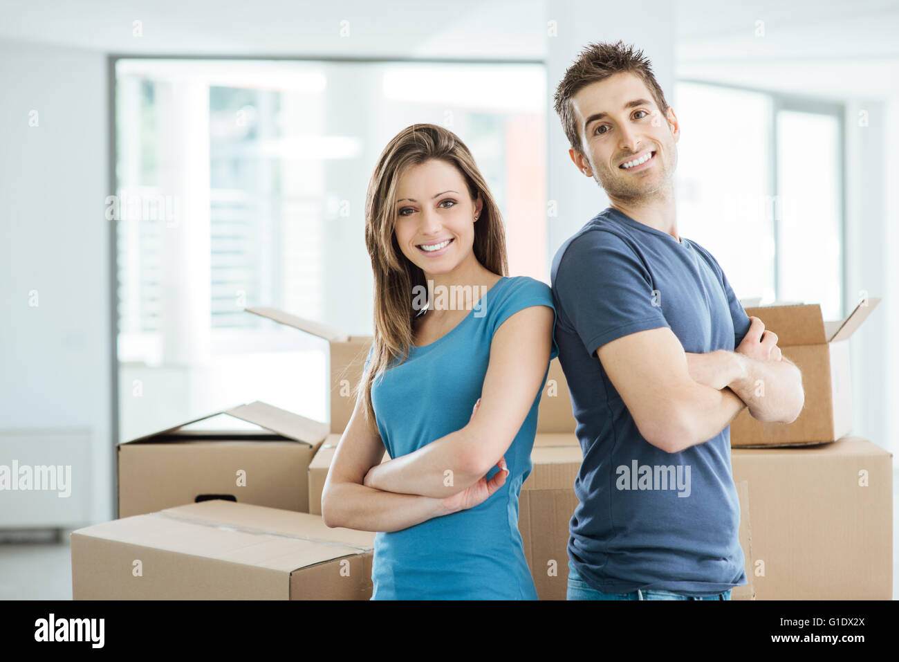 Smiling loving couple posing in their new house back to back surrounded by carton boxes - Stock Image