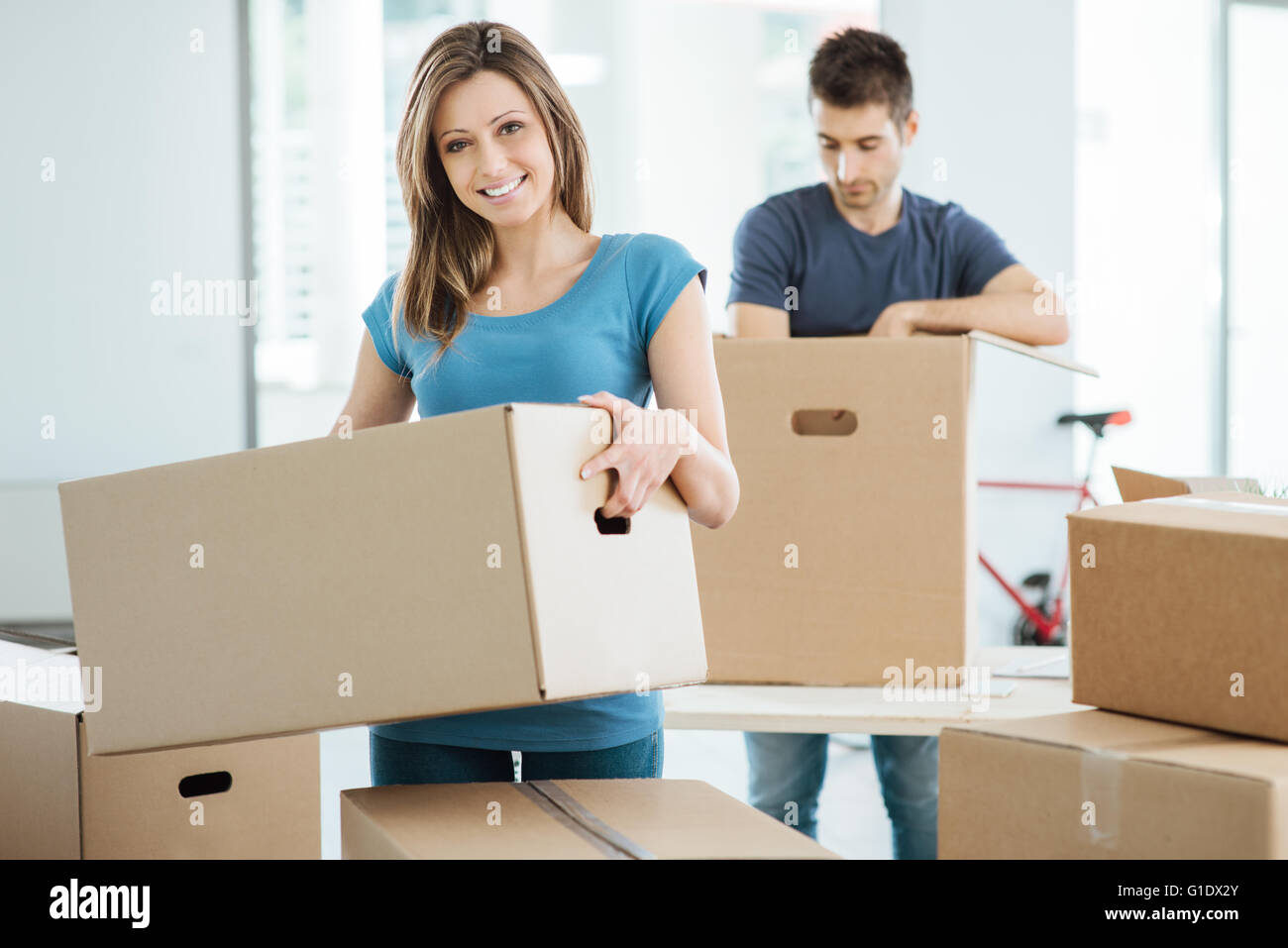 Young happy couple moving in their new house and unpacking boxes, she is carrying a carton box and smiling at camera Stock Photo