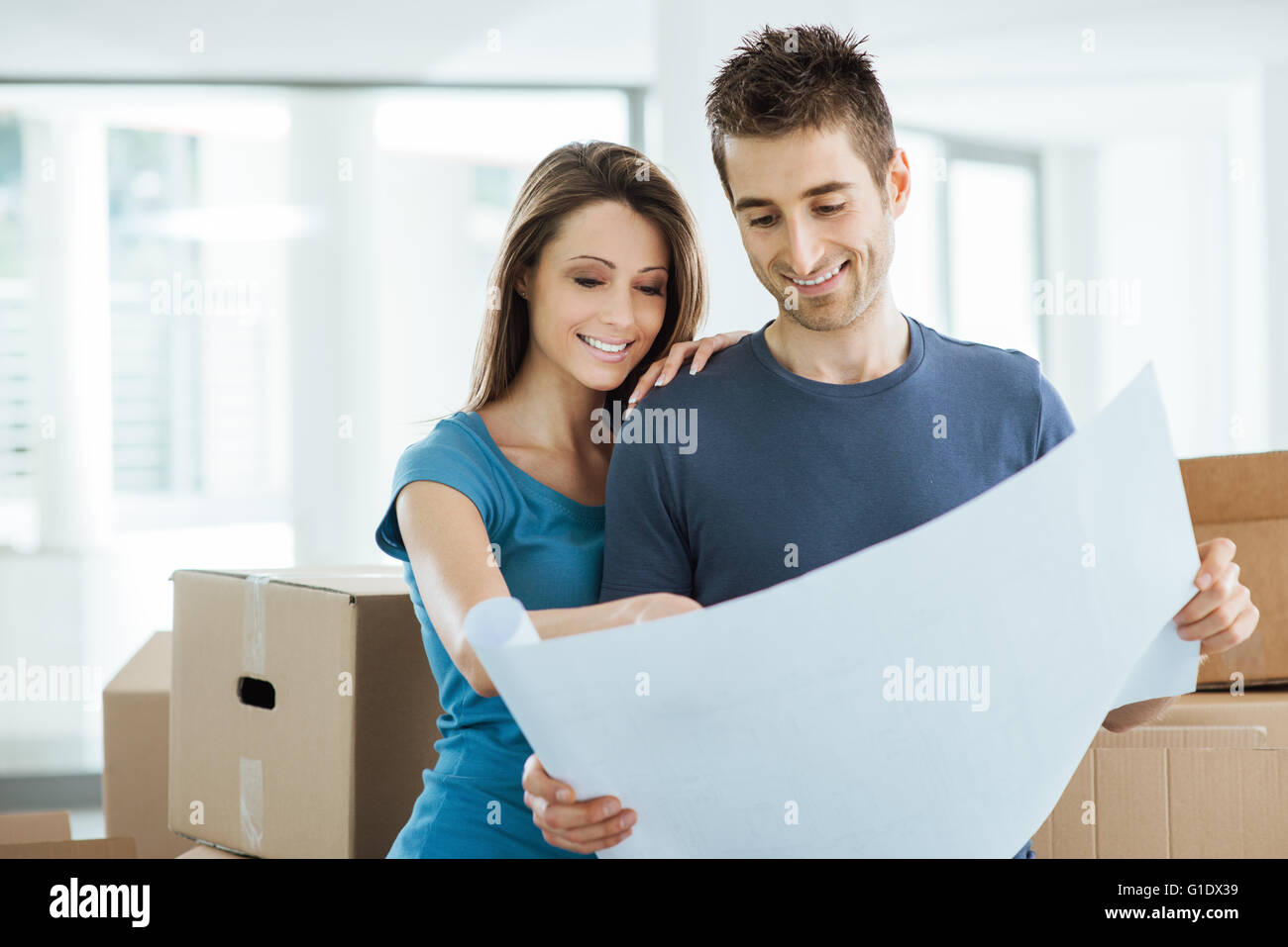 Young happy couple holding a project and planning their new house, relocation and renovation concept Stock Photo