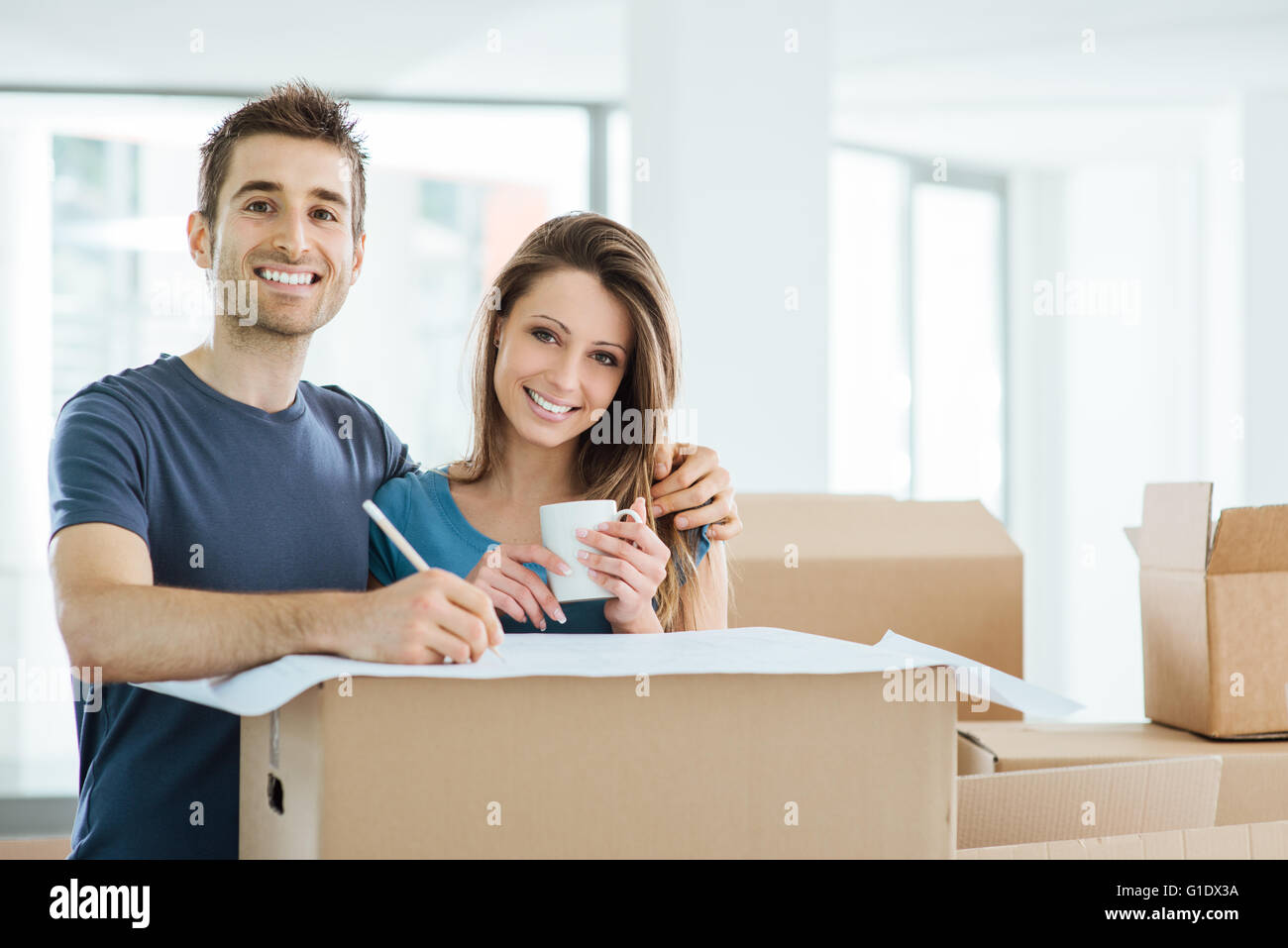 Happy couple planning and designing their new house surrounded by carton boxes, he is drawing on a project - Stock Image