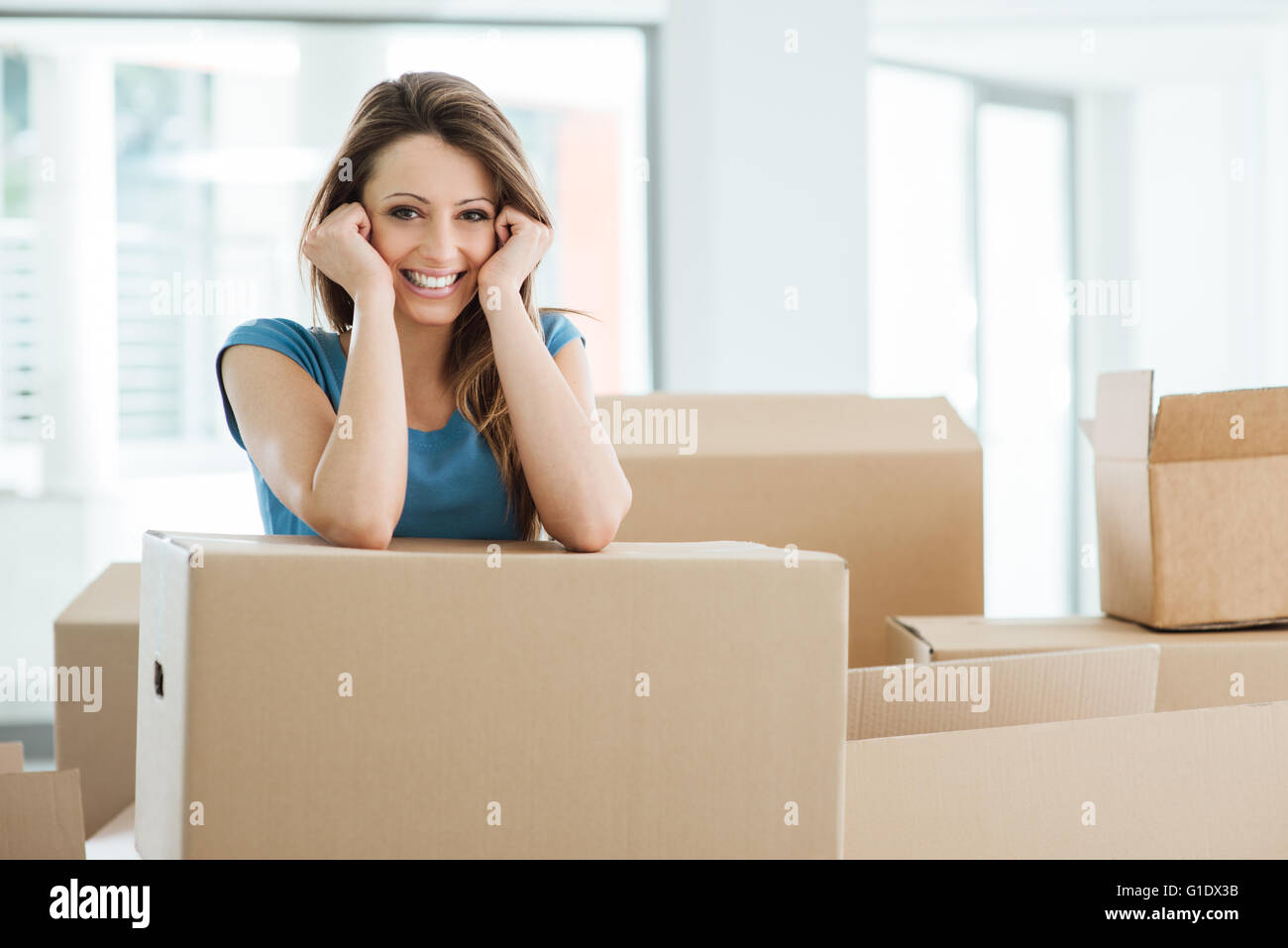 Smiling young woman moving in her new house and leaning on a cardboard box - Stock Image