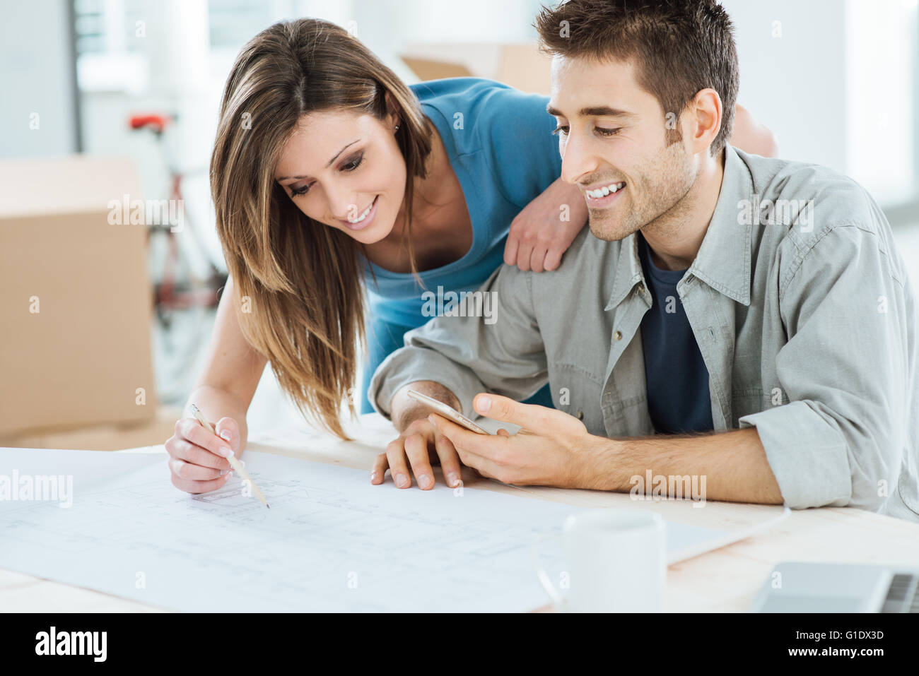 Young couple planning their new dream house, he is sitting at desk and she is drawing on a project, carton boxes - Stock Image