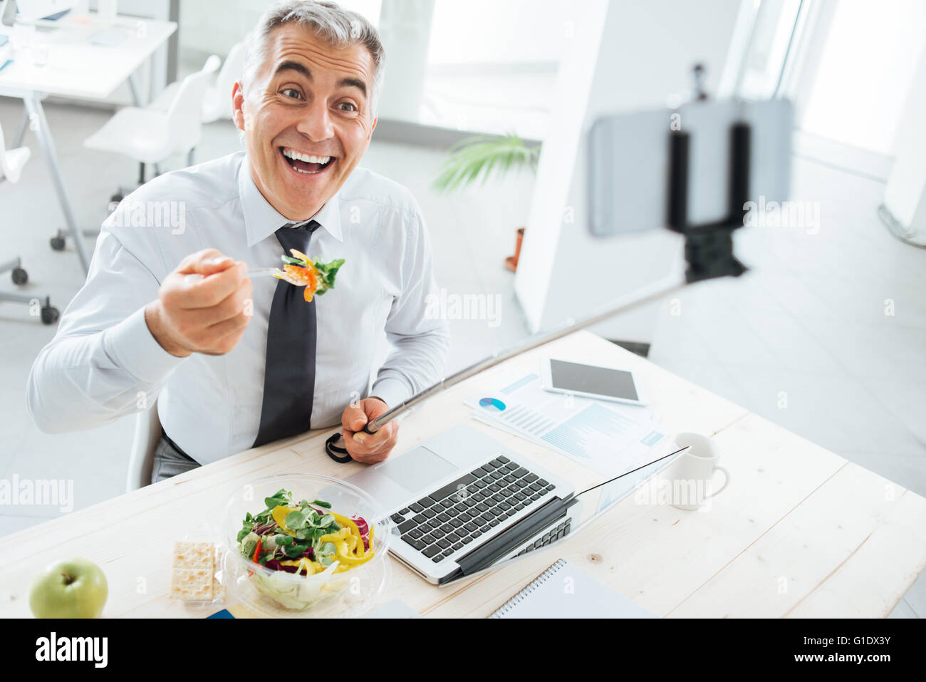 Happy smiling businessman at office desk having a lunch break and taking selfies with a selfie stick and a smart - Stock Image