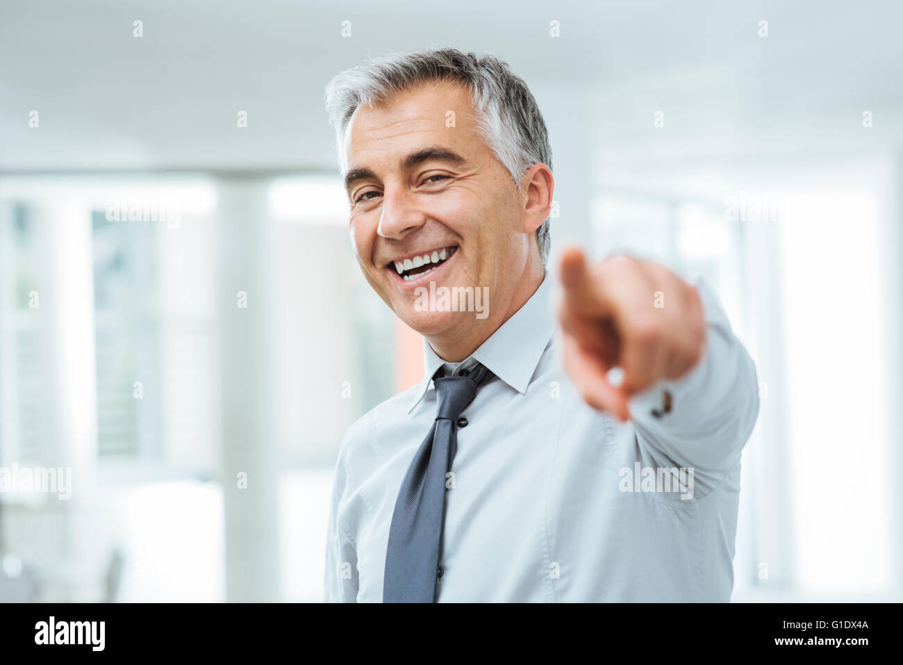 Cheerful confident businessman pointing at camera, recruitment and choice concept - Stock Image