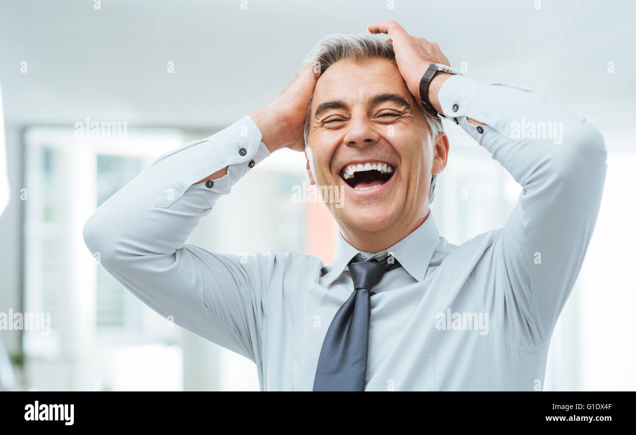 Cheerful careless businessman laughing and touching his forehead - Stock Image