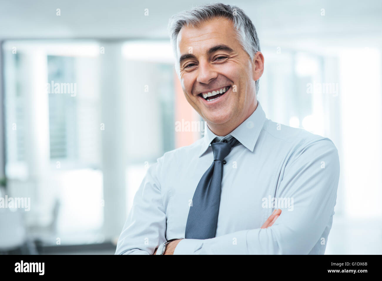 Successful businessman posing with crossed arms and smiling at camera - Stock Image