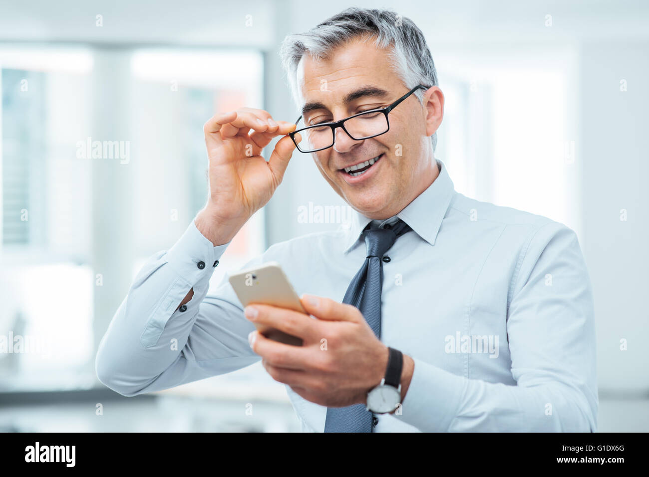 Smiling businessman with eyesight problems, he is adjusting his glasses and reading something on his mobile phone - Stock Image