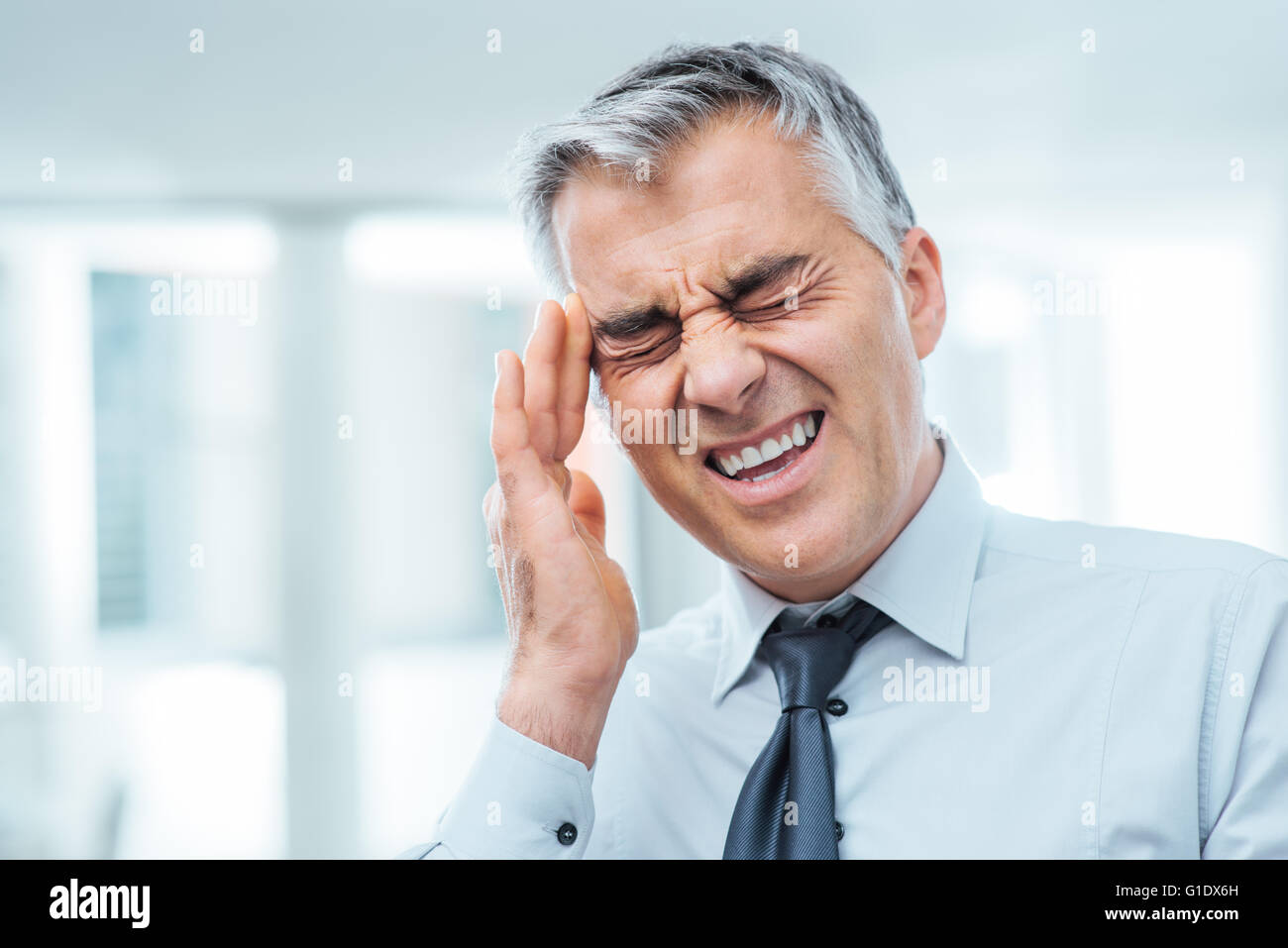 Suffering businessman having a terrible headache and touching his temples, stress and illness concept - Stock Image