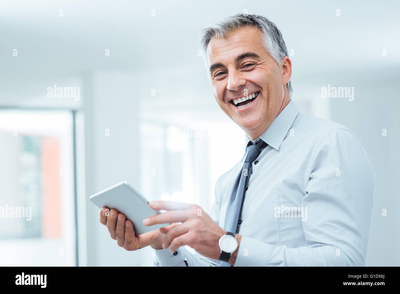 Smiling confident businessman looking at camera and using a digital touch screen tablet - Stock Image
