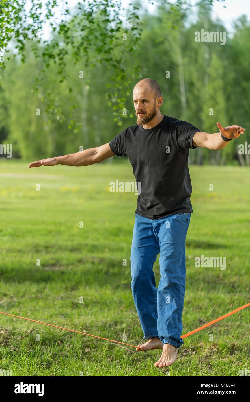 Man practising slack line in the park - Stock Image