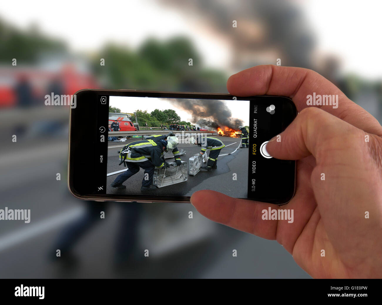 Onlookers take picture with a mobile phone camera, of an accident, symbolic image, photomontage, photo composition, - Stock Image