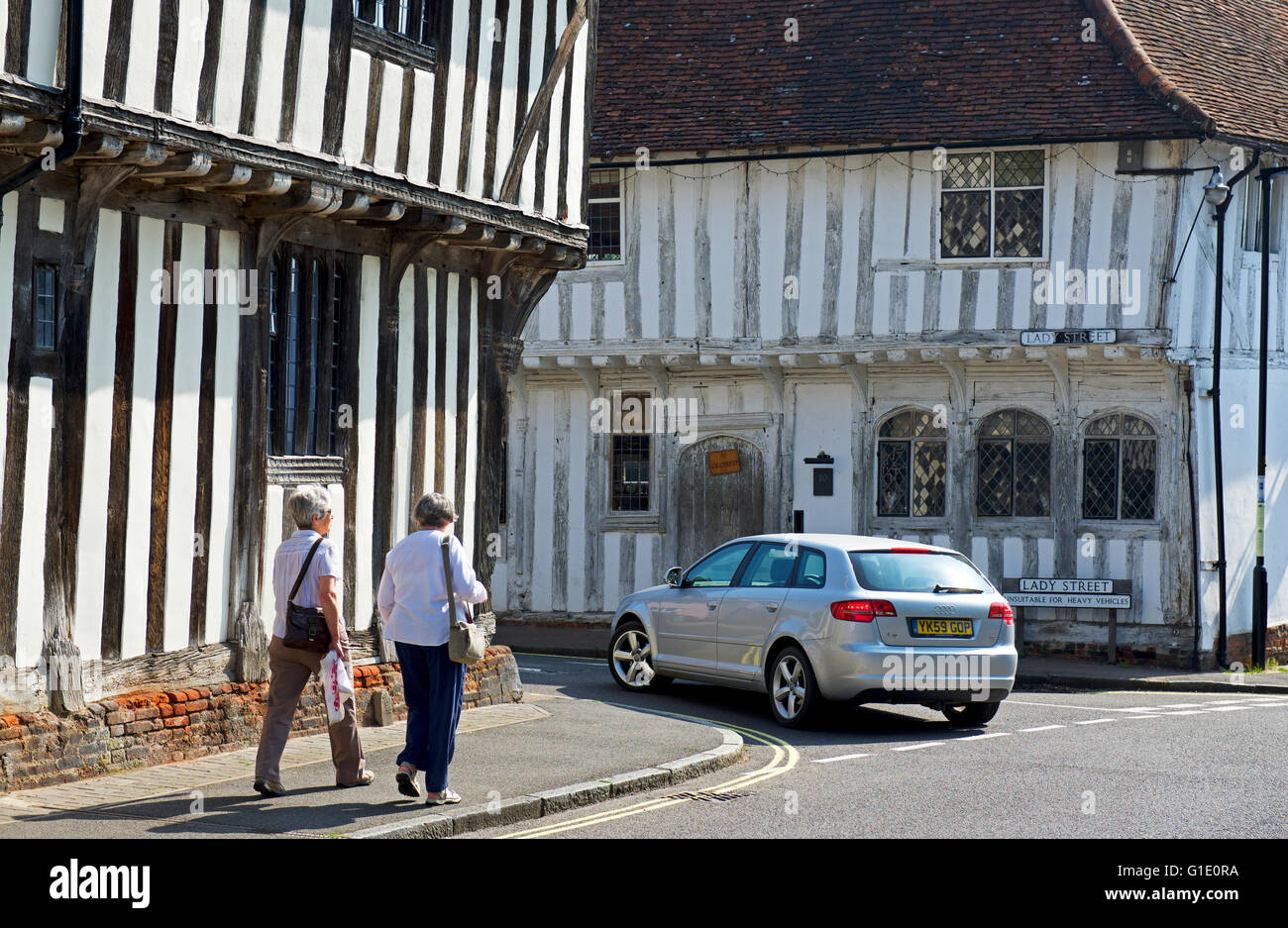 Two women walking past half-timbered buildings in the village of Lavenham, Suffolk, England UK - Stock Image