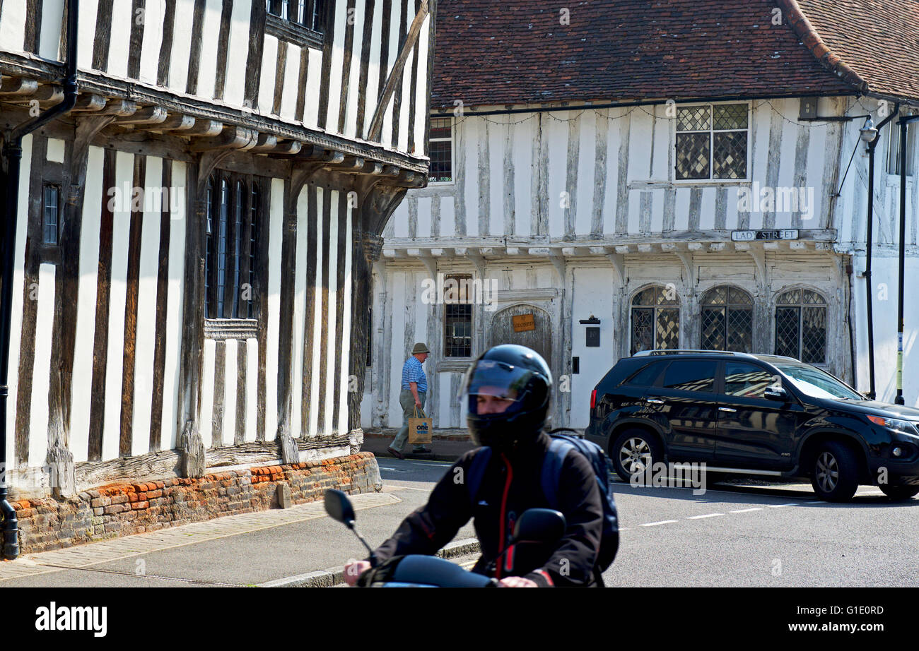 Car and motorbike in the village of Lavenham, Suffolk, England UK Stock Photo