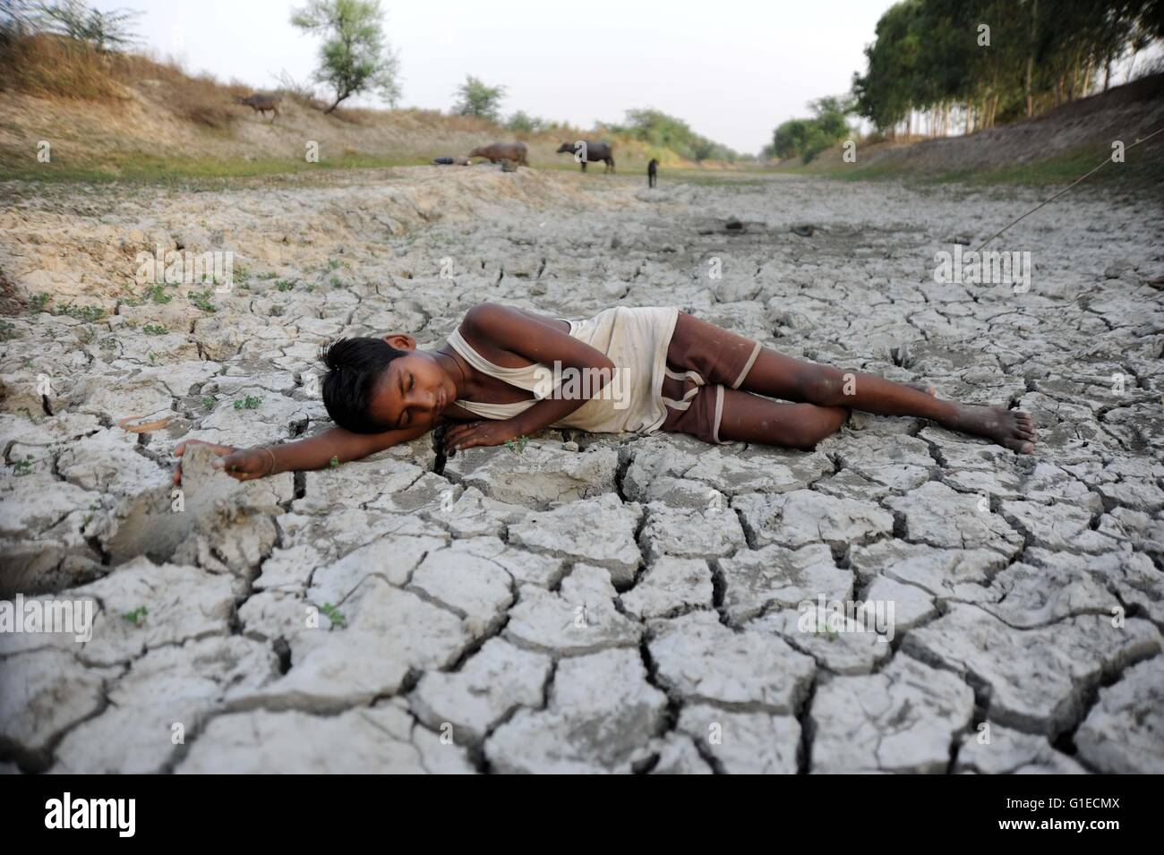 Allahabad, India. 14th May, 2016. A child lays down on dry bed of parched River Varuna at Phoolpur. Much of India - Stock Image
