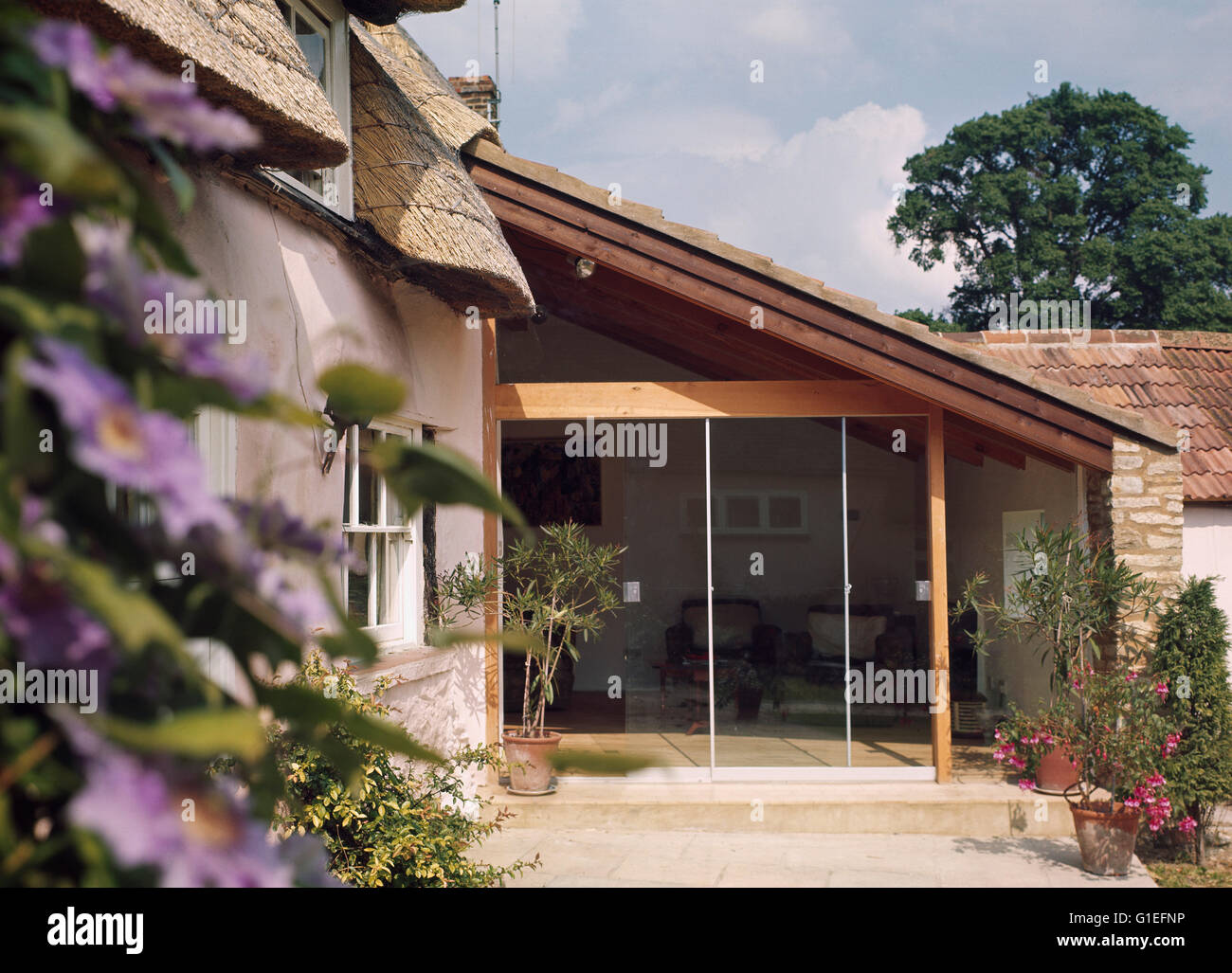 Cottage Extension Haddenham. Exterior view of a cottage extension with a sloped roof and ceiling to floor windows. - Stock Image