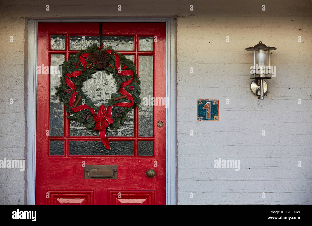 Christmas Garland On Door. Green Wreath With Red Ribbon Hanging On Red And Glass  Door