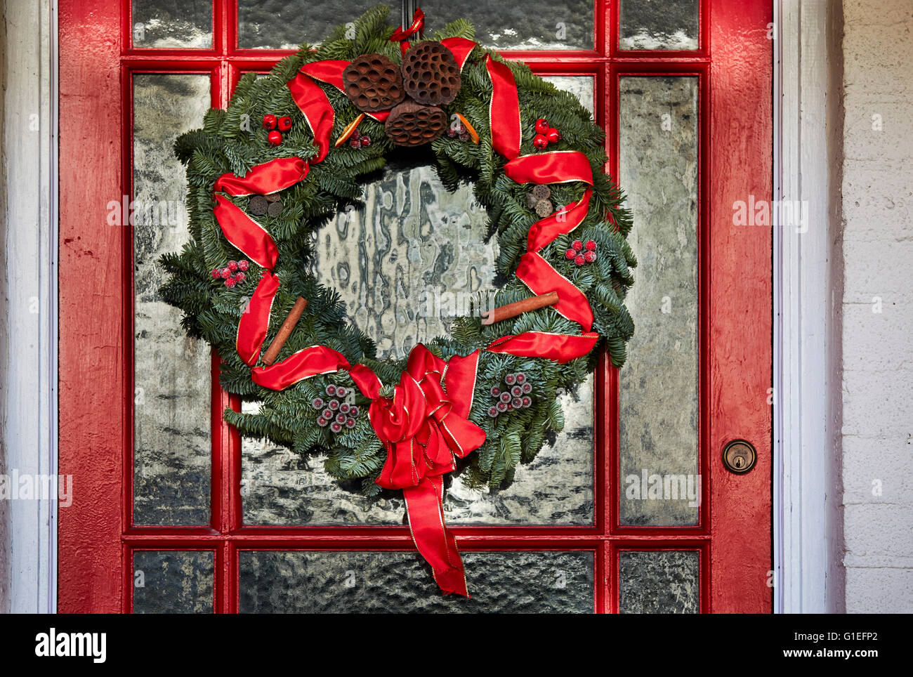 Christmas Garland On Door. Green Wreath With Red Ribbon Hanging On Red And Glass  Door.