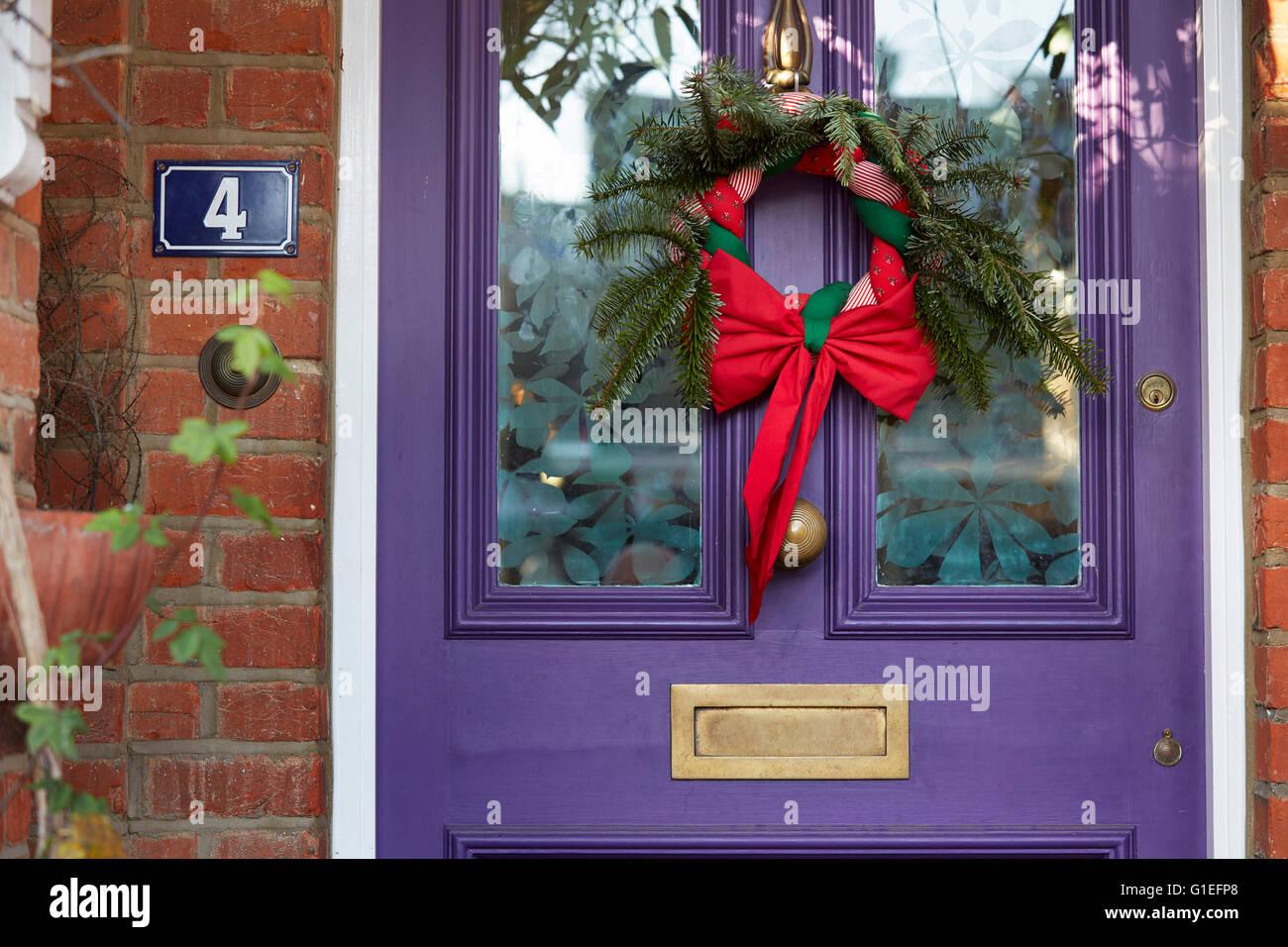Christmas Garland On Door Wreath Hanging On Purple Door Stock Photo