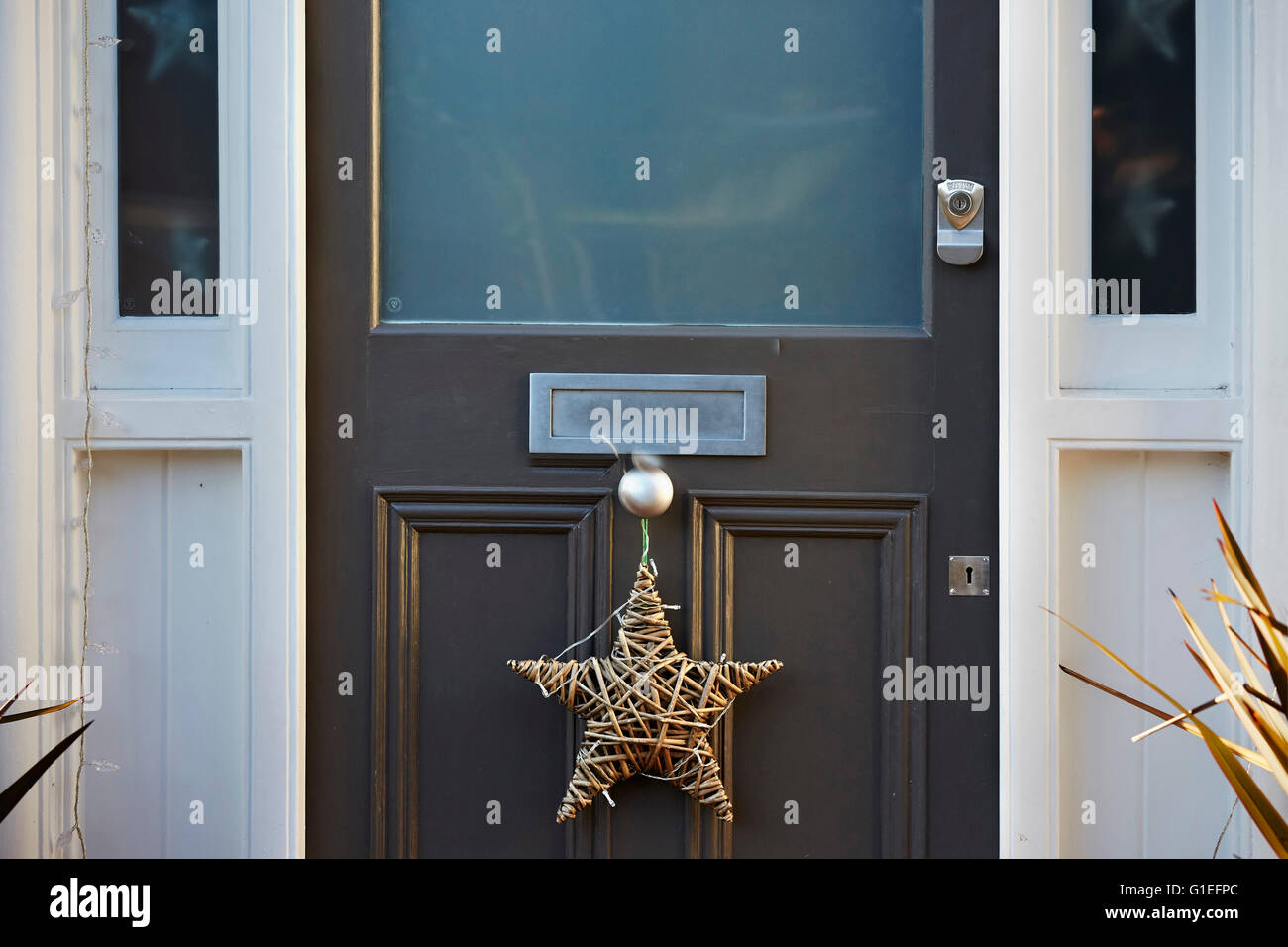 Christmas Garland on Door. Star shaped garland hanging from doorknob. - Stock Image