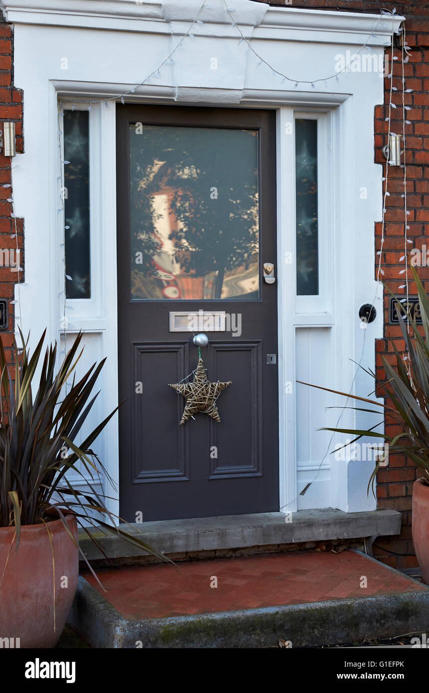 Christmas Garland on Door. Star shaped garland hanging off a doorknob on a grey door. - Stock Image