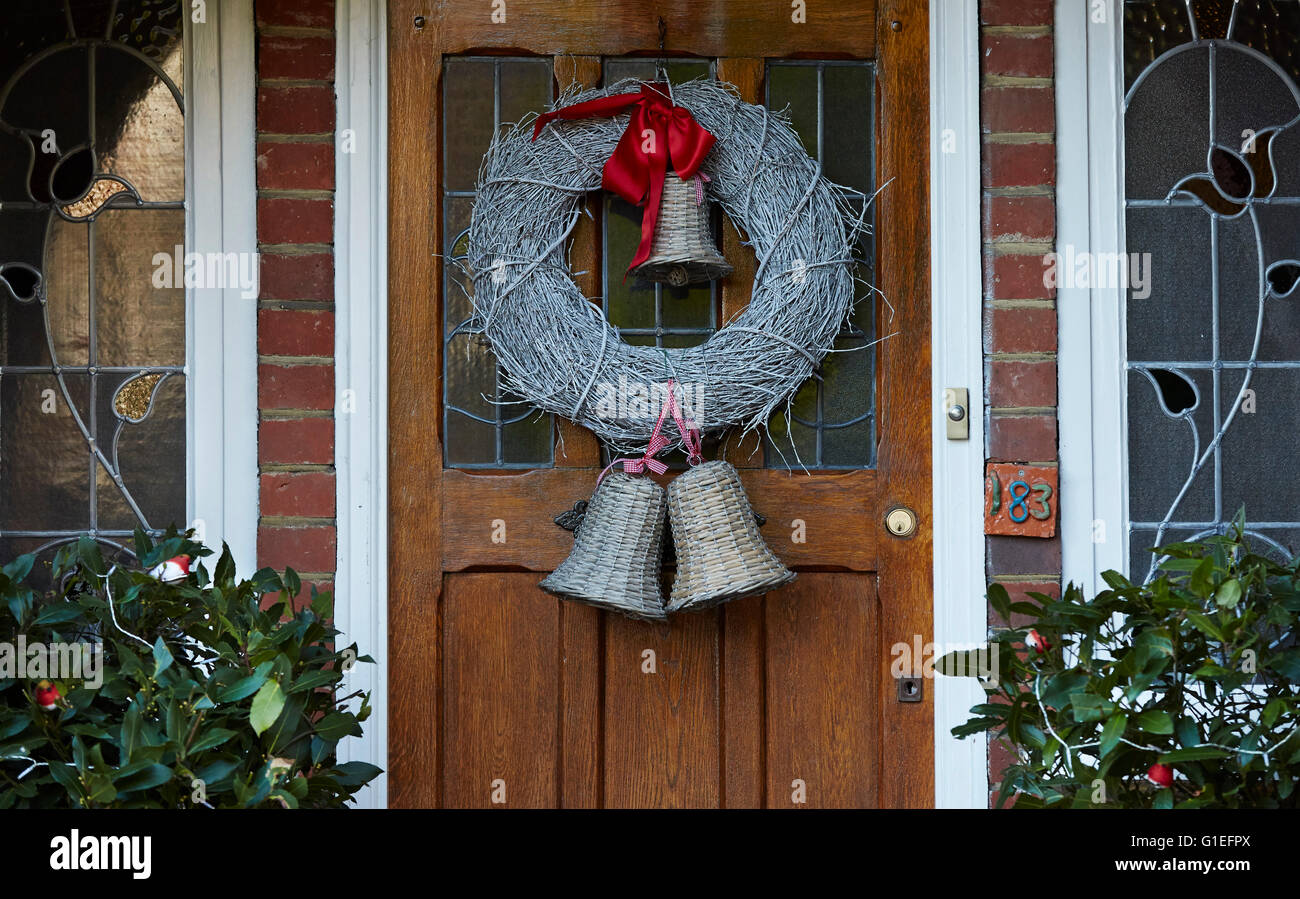 Christmas Garland on Door. White garland with bells attached hanging on wood door. - Stock Image