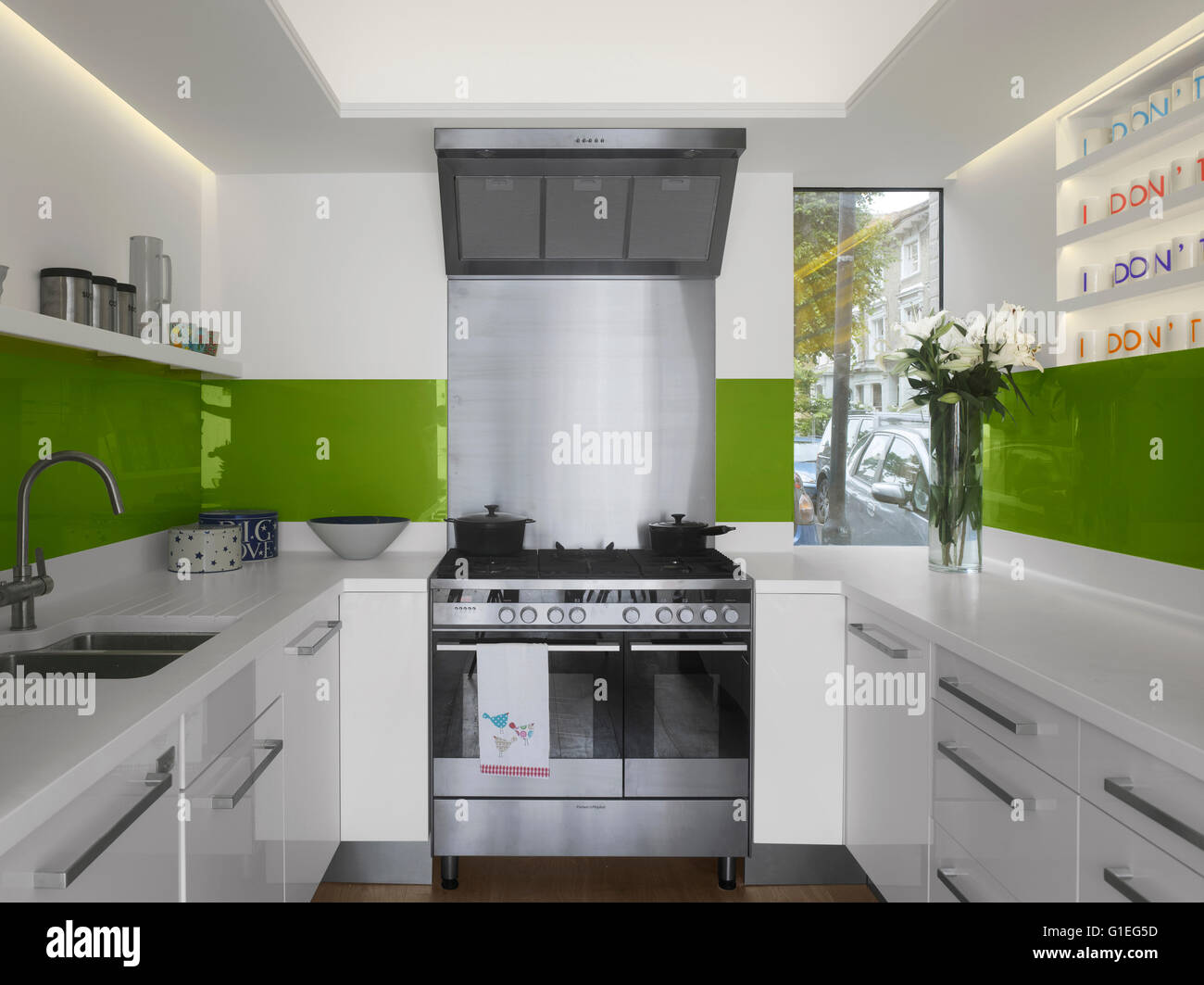 Modern Family home, Shepherds Bush, London. Kitchen with modern sleek features and stainless steel appliances. Green - Stock Image