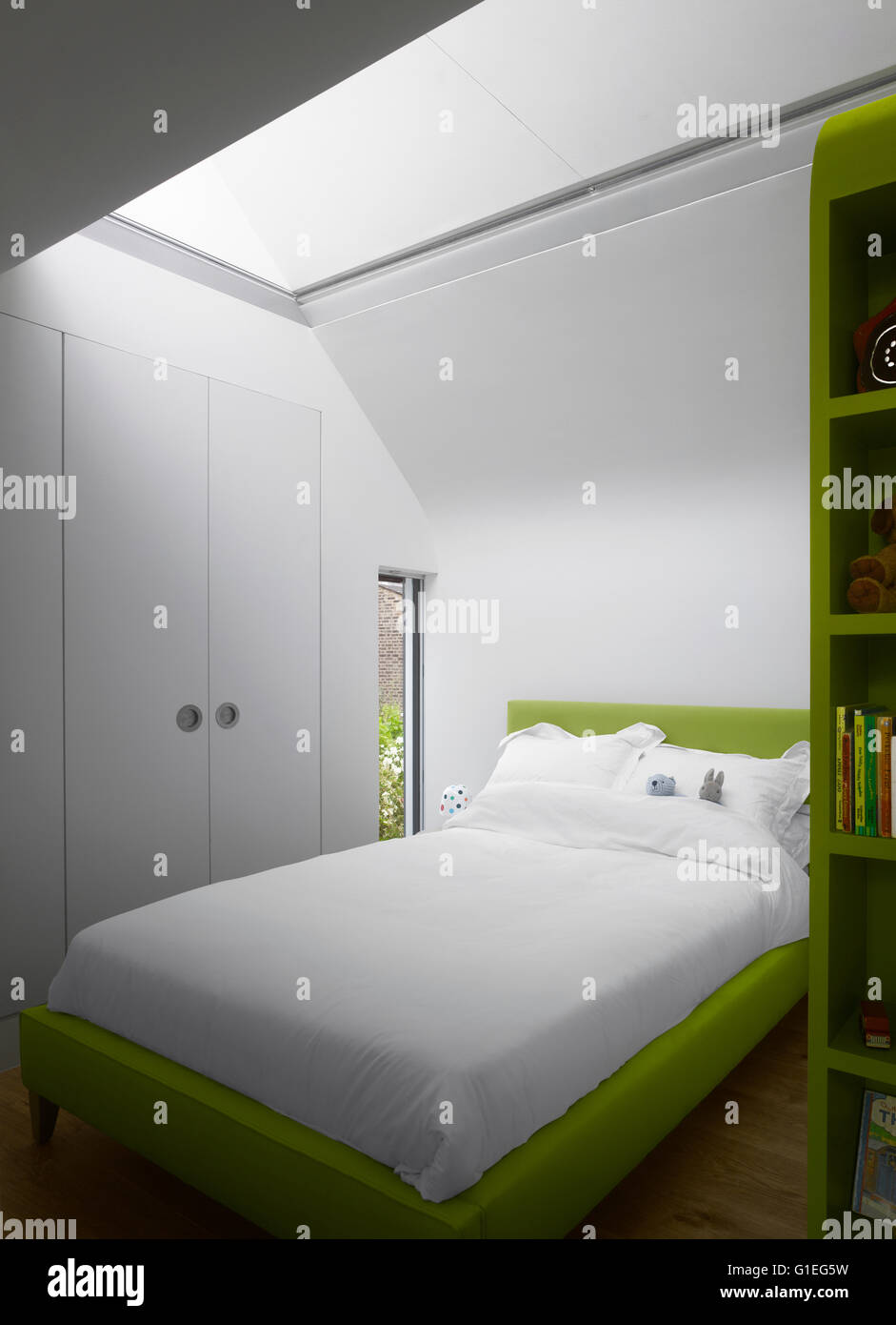 Modern Family home, Shepherds Bush, London. Bedroom with white linens and green accents. - Stock Image