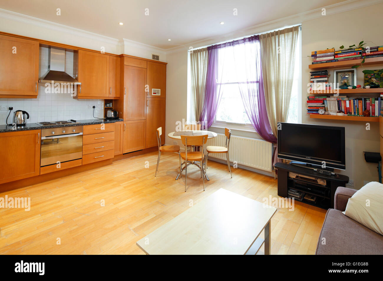 Belsize Lane, Hampstead. Open plan living room and kitchen with wood floors and large window. Stock Photo